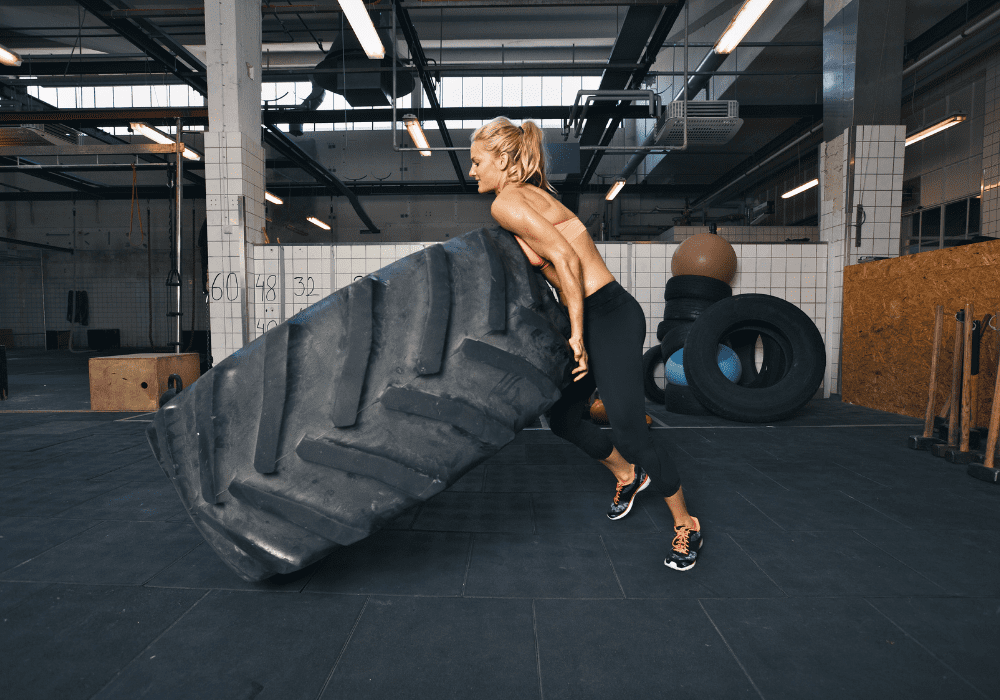 Woman Flipping Tires As Part Of Her HIIT Routine