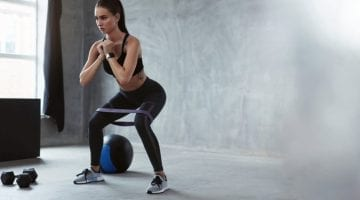 Woman doing body squats for strength training exercises at home