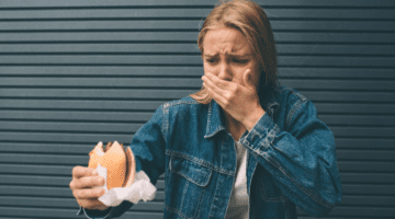 Woman eating food that aggravates her leaky gut syndrome