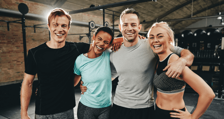 4 Friends pose for a picture in the gym after their high intensity interval workout.
