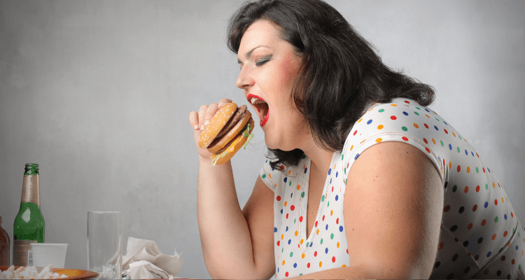 Low energy, obese woman eating excessive junk food