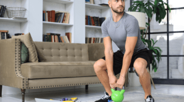 Man performing kettlebell workout from his living room