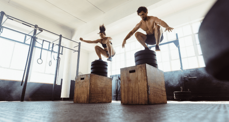 Man and Woman perform high intensity box jumps as opposed to traditional cardio
